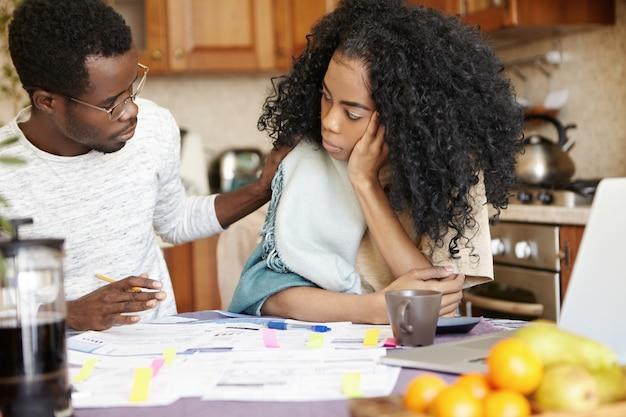 Triste donna africana con acconciatura afro che sembra triste e infelice a causa di problemi finanziari nella sua famiglia mentre suo marito seduto accanto a lei, toccandole la spalla, cercando di tirarla su di morale