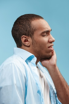 Sad afro-american man is having toothache. against blue space