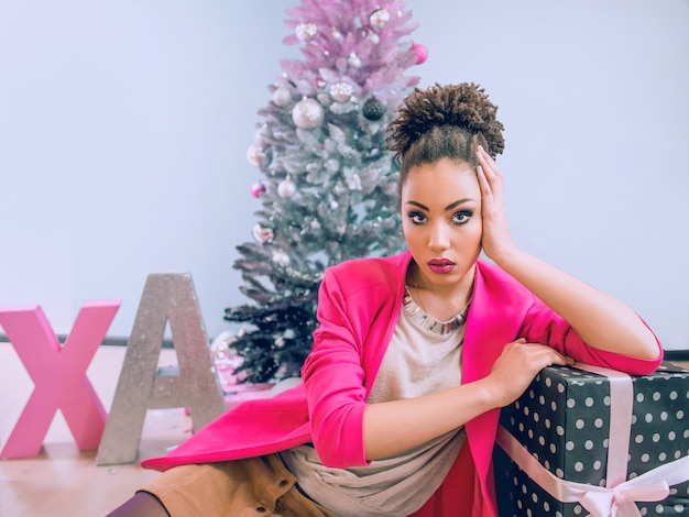 Грустная афроамериканка у елки разочарована рождественским подарком