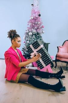 Грустная афроамериканка разочарована рождественским подарком
