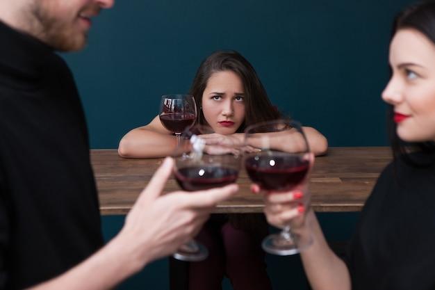 술집에서 슬픈 혼자 여성. 질투 배경. 삼각 관계, 속임수 관계. 파란색 배경, 외로움 개념에 초점을 맞춘 불행한 배신당한 여자