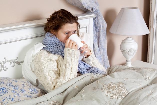 白いセーターと青いスカーフを着た悲しい一人の若い女性は、冷たい病気を感じ、ベッドで家で休んでいます。彼女の薬を飲んで、乳首をしようとします。屋内スタジオショット。