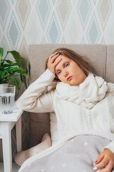 Грустная одна молодая женщина в белом свитере и шарфе с красным носом, чувствуя головную боль