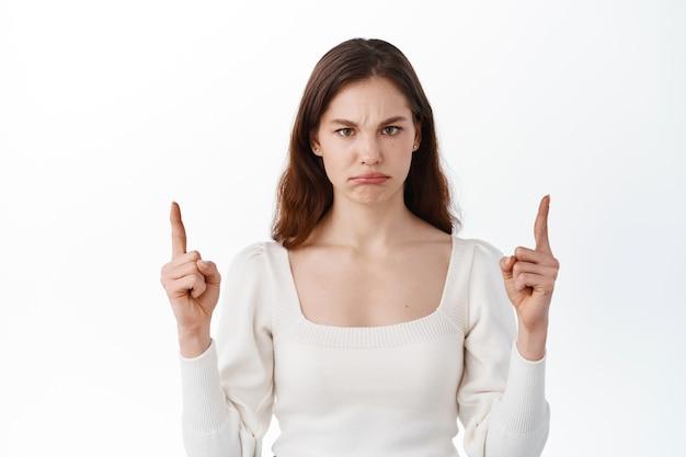 悲しくて怒っている若い女性が指を上に向け、あなたを責め、不機嫌になり、眉をひそめ、不公平または悪い何かを見せ、不平を言い、白い壁に立っている