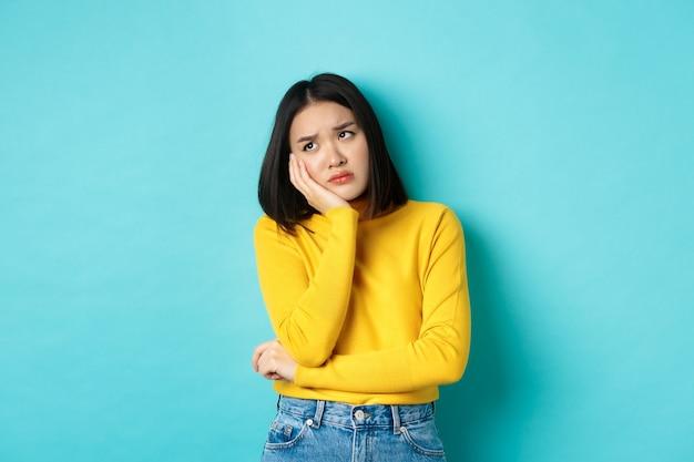 Грустная и скучающая азиатская девочка-подросток, опираясь на ладонь, глядя в верхний левый угол с одиноким и расстроенным выражением лица, стоя на синем фоне.