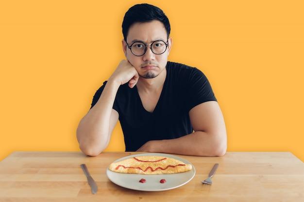 슬프고 지루한 아시아 남자는 오믈렛의 집에서 만든 아침 식사 세트를 먹고 있습니다.
