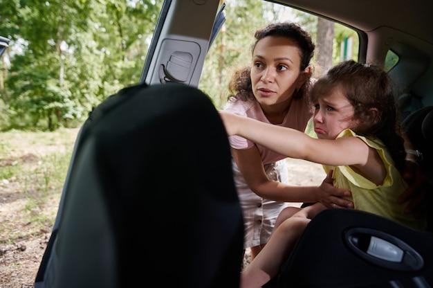 チャイルドシートで悲しくて泣いている女の赤ちゃんが指を指して、車の外の何かに母親を見せている
