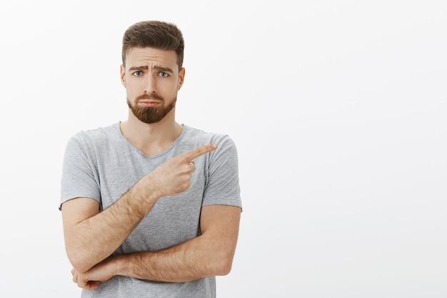 Грустный и милый очаровательный бородатый мужчина-модель в серой футболке, хмурясь, делает мрачное лицо с нахмуренными бровями, дуется, указывая вправо, выражая сожаление и зависть, недовольно стоящая над белой стеной