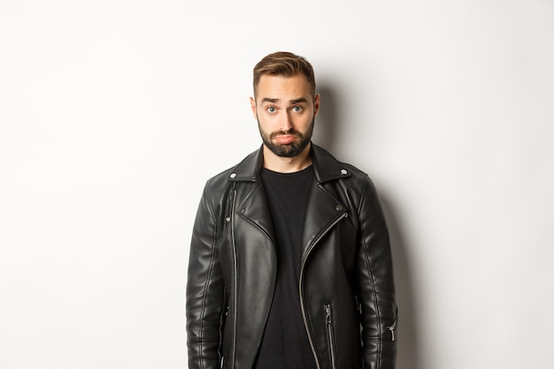 Грустный и милый парень в кожаной черной куртке надувается, глупо смотрит в камеру, стоя на белом фоне.