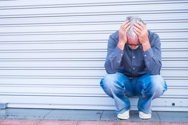 슬프고 우울한 남자가 사업 활동을 끝내고 일자리를 잃습니다. 오래 된 사업가 deemployee outisde 가까운 상점 또는 저장소
