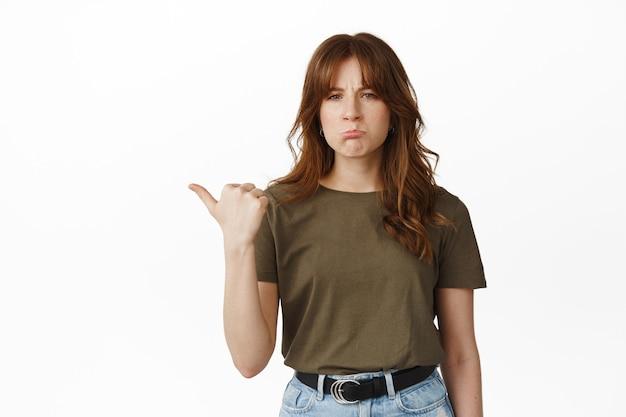 왼쪽을 가리키는 슬프고 실망한 여학생, 찡그린 얼굴을 하고 불쾌한 표정을 짓고, 무언가에 대해 불평하고, 불공평하거나 후회하고, 흰색 위에 서 있다