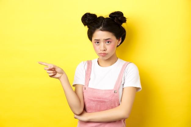 グラマーメイク、不公平に眉をひそめ、ロゴを左に向け、失望しているように見え、黄色の上に立っている、悲しくて暗いアジアの女の子。