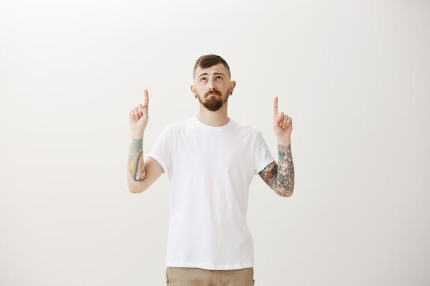 Грустный и мрачный хипстерский парень с сожалением смотрит на промо, указывая пальцем вверх