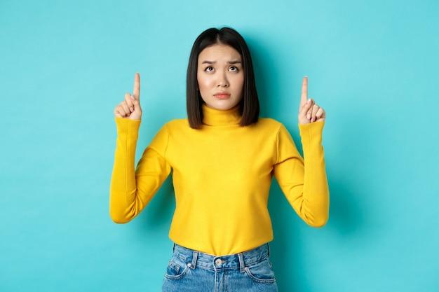 悲しくて憂鬱な韓国人女性が指を上に向け、嫉妬と動揺した顔で見て、青の上に立っています。
