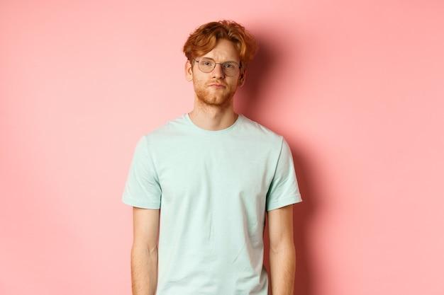 ピンクの背景の上に立って、退屈で面白くないカメラを見つめて、tシャツとメガネで悲しくて暗い赤毛のひげを生やした男