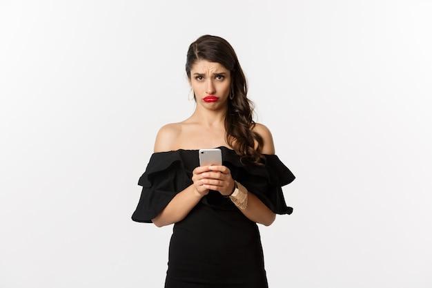 白い背景の上に立って、携帯電話を使用して失望している、黒いドレスを着た悲しくて憂鬱な女性。