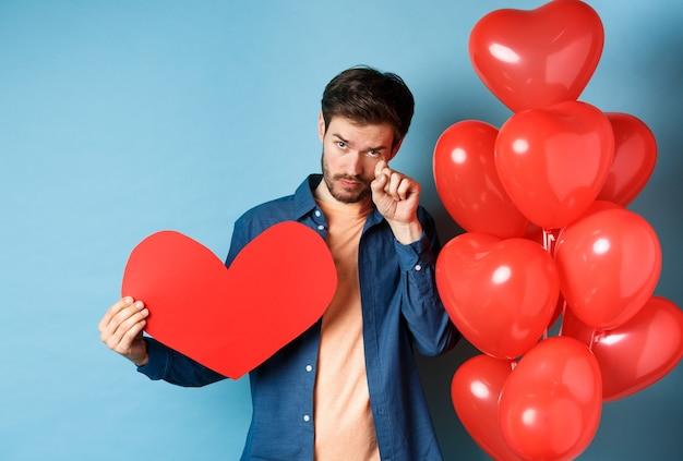 슬프고 상심 한 남자가 울고, 눈물을 닦고, 붉은 마음과 풍선, 발렌타인 데이, 파란색 배경에 이별.