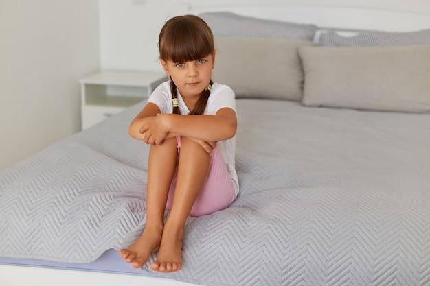 침대에 앉아 있는 슬프고 어린 소녀, 흰색 티셔츠와 장미 셔츠를 입은 아이가 카메라를 바라보며 슬픔을 표현하고 집의 밝은 방에서 혼자 포즈를 취합니다.