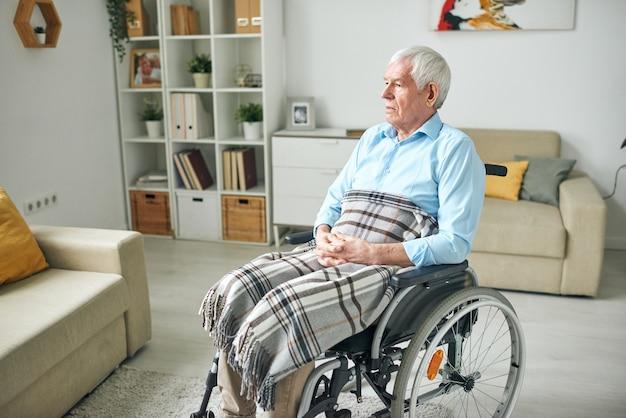 Грустный и безмятежный старший инвалид с клетчатым пледом на коленях сидит в инвалидной коляске у дивана дома