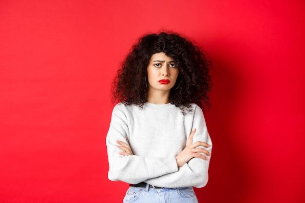 Грустная и взволнованная кавказская женщина хмурится, скрестив руки на груди и выглядит обеспокоенной, плохо себя чувствует, стоит на красном фоне