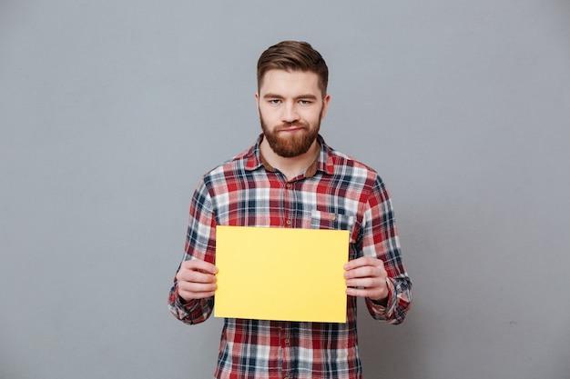 Грустный злой бородатый мужчина держит чистый лист бумаги