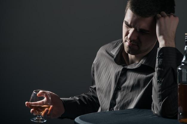 슬픈 냉담한 젊은 남자가 검은 색 표면에 알코올 음료를 마신다