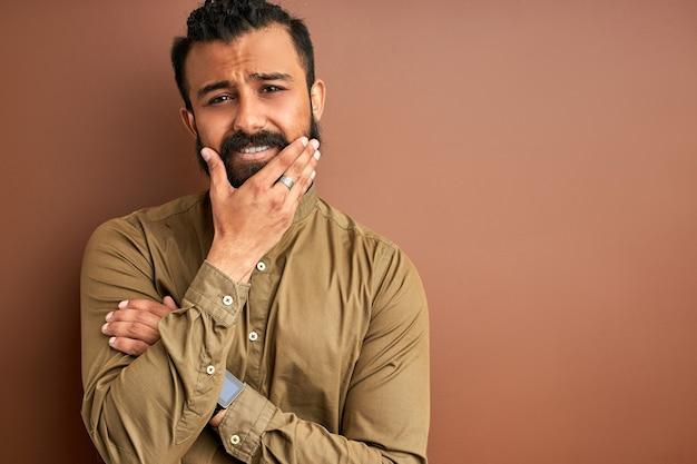 Грустный арабский мужчина держит лицо изолированным, чувствует себя плохо, с разочарованным лицом, изолированным на коричневом фоне