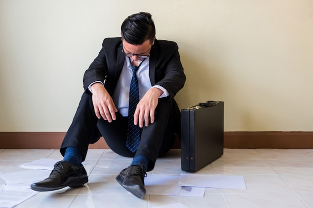 Sad asian businessman sit on floor