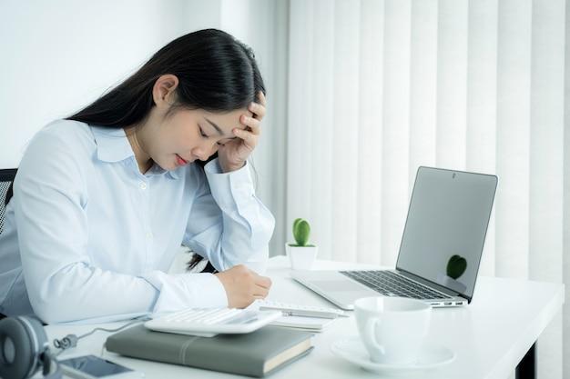 Унылый азиатский работник коммерсантки недоволен работая с скучно на компьтер-книжке и диаграмме в офисе устало, концепция синдрома офиса.