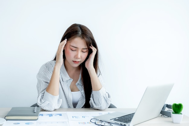 Грустный азиатский сотрудник бизнес-леди недоволен работой со скучным на ноутбуке и графиком в офисе