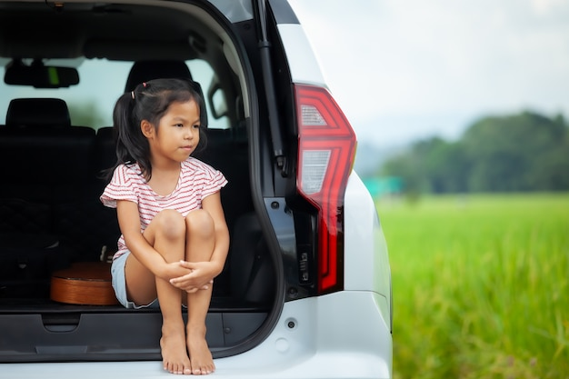 Sad asian child girl sitting alone in a car trunk and looking to the nature outside