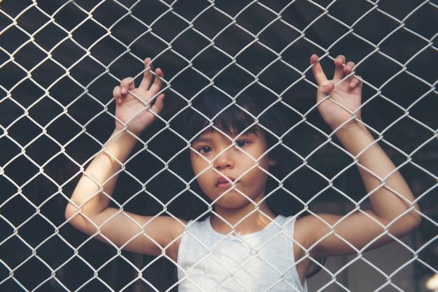 Грустная азиатская девчонка одна в клетке была заключена в тюрьму без свободы или отсутствия свободы