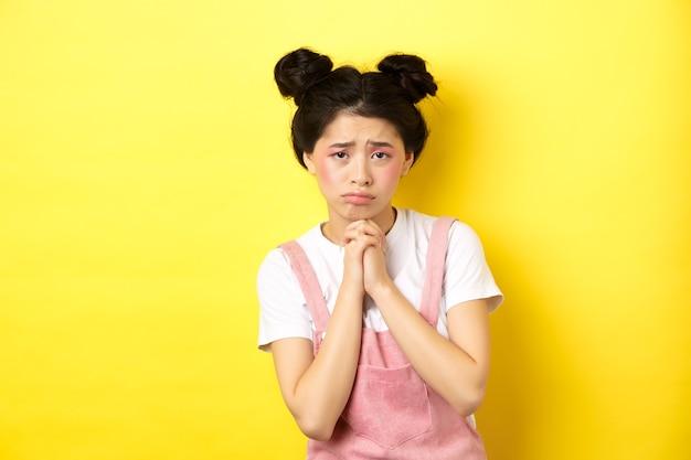 助けを求めて、あなたに懇願し、やめなさい、そして泣き言を言って、黄色の上に立っている悲しいアジアの女の子。