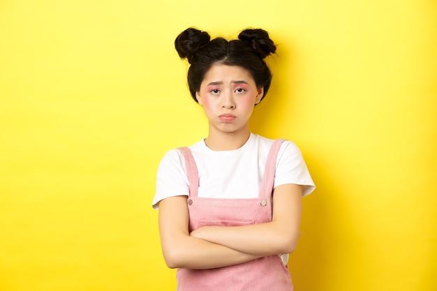 悲しいアジアの十代の少女は、やめなさい、胸に腕を組んで、ふくれっ面と眉をひそめ、不公平なことに不平を言い、黄色に立ち向かいます。