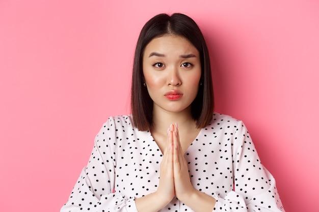 助けを求める悲しいアジアの女性、懇願するジェスチャーで手で物乞い、カメラを見つめる、好意が必要、ピンクの上に立つ