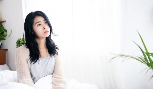 침대에 누워 있는 슬픈 아시아 여성, 혼자 생각하는 걱정, 불행한 여성
