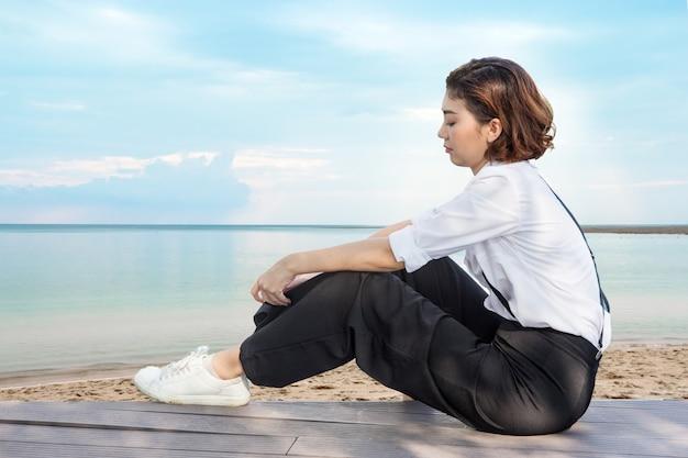 海の景色の海岸に座っている悲しいアジアの女性