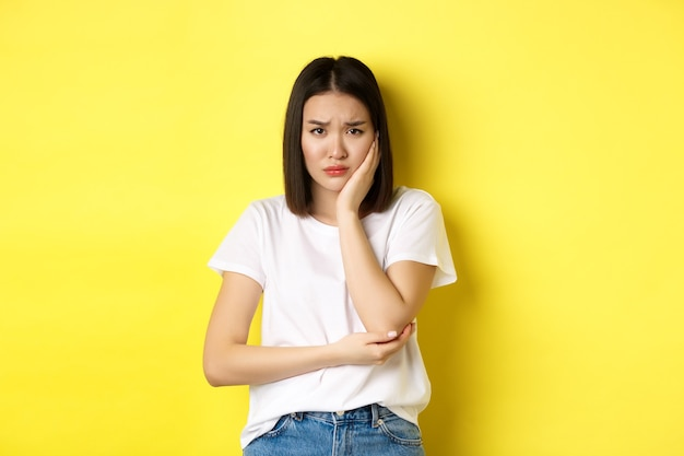 Sad asian woman touching cheek and frowning, having toothache, need see dentist, standing gloomy against yellow background.