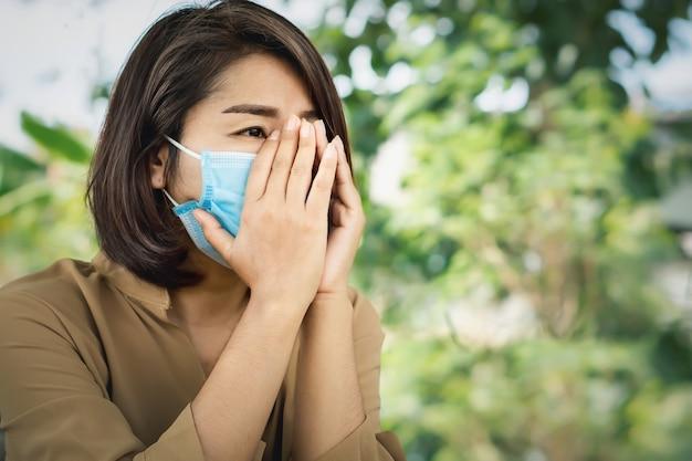 Sad asian woman wearing protective mask crying alone