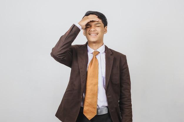 Грустный азиатский молодой бизнесмен, имеющий головную боль