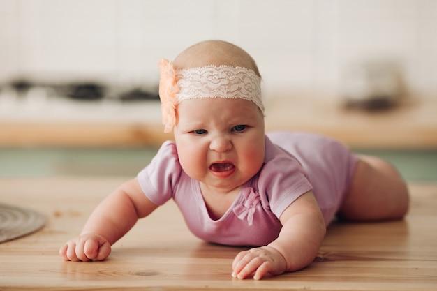 Sad baby lying on floor and crying