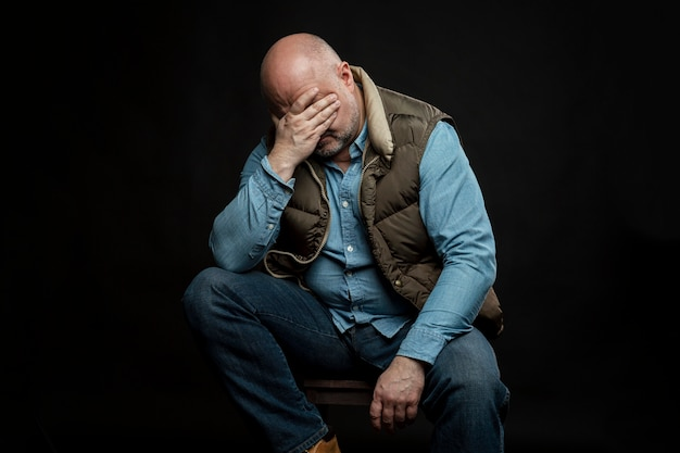 Sad bald man in jeans on a black wall. vertical. unemployment and financial problems in the global crisis during the coronavirus pandemic.