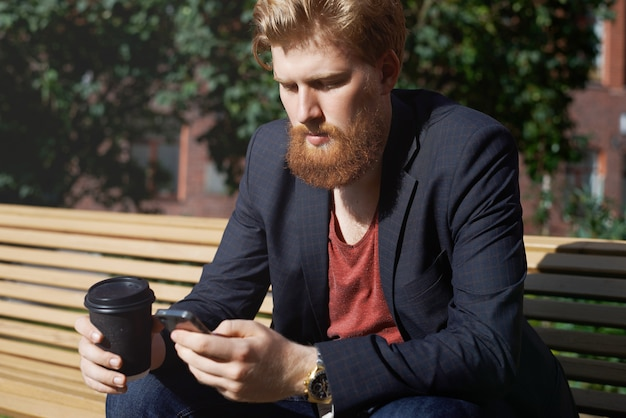 Sad beard man uses phone to find new job