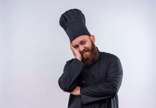 Un uomo chef barbuto triste in uniforme nera pensando e tenendo la mano sul viso su un muro bianco