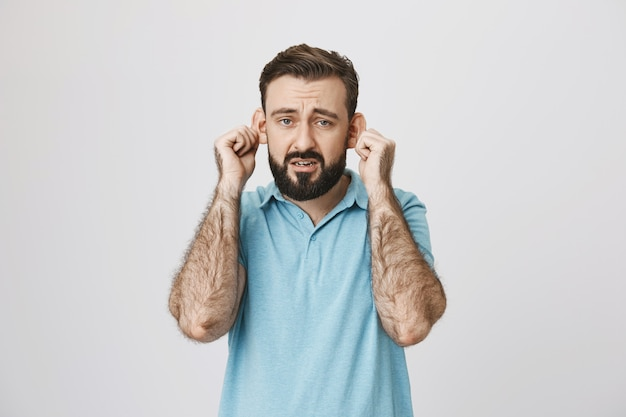 Sad bearded guy showing his ears and complaining