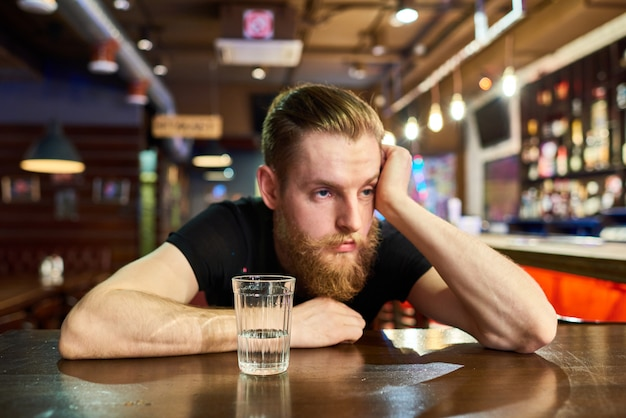 Sad bearded man getting drunk in bar