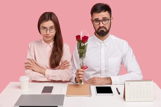 Sad bearded man has discontent look as recieves refusal from woman to date, holds red roses