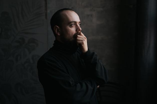 Унылый бородатый мужчина смотрит в окно. мечта, размышления и мышление концепции. вид внутреннего профиля