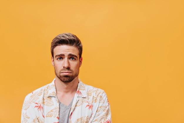 유행 인쇄 셔츠와 격리 된 오렌지 벽에 카메라를 찾고 회색 티셔츠에 파란 눈을 가진 슬픈 수염 난된 남자