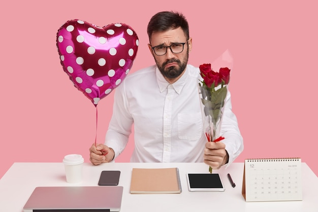 Sad bearded young male carries balloon, roses, wears glasses